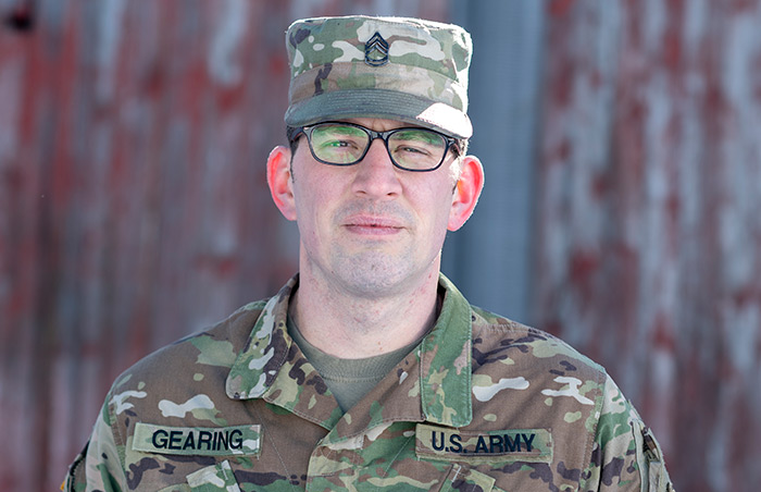 National Guard Dairy Farmer in front of barn