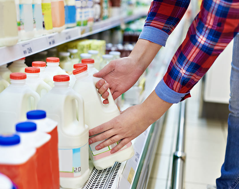 Consumer with choosing milk.